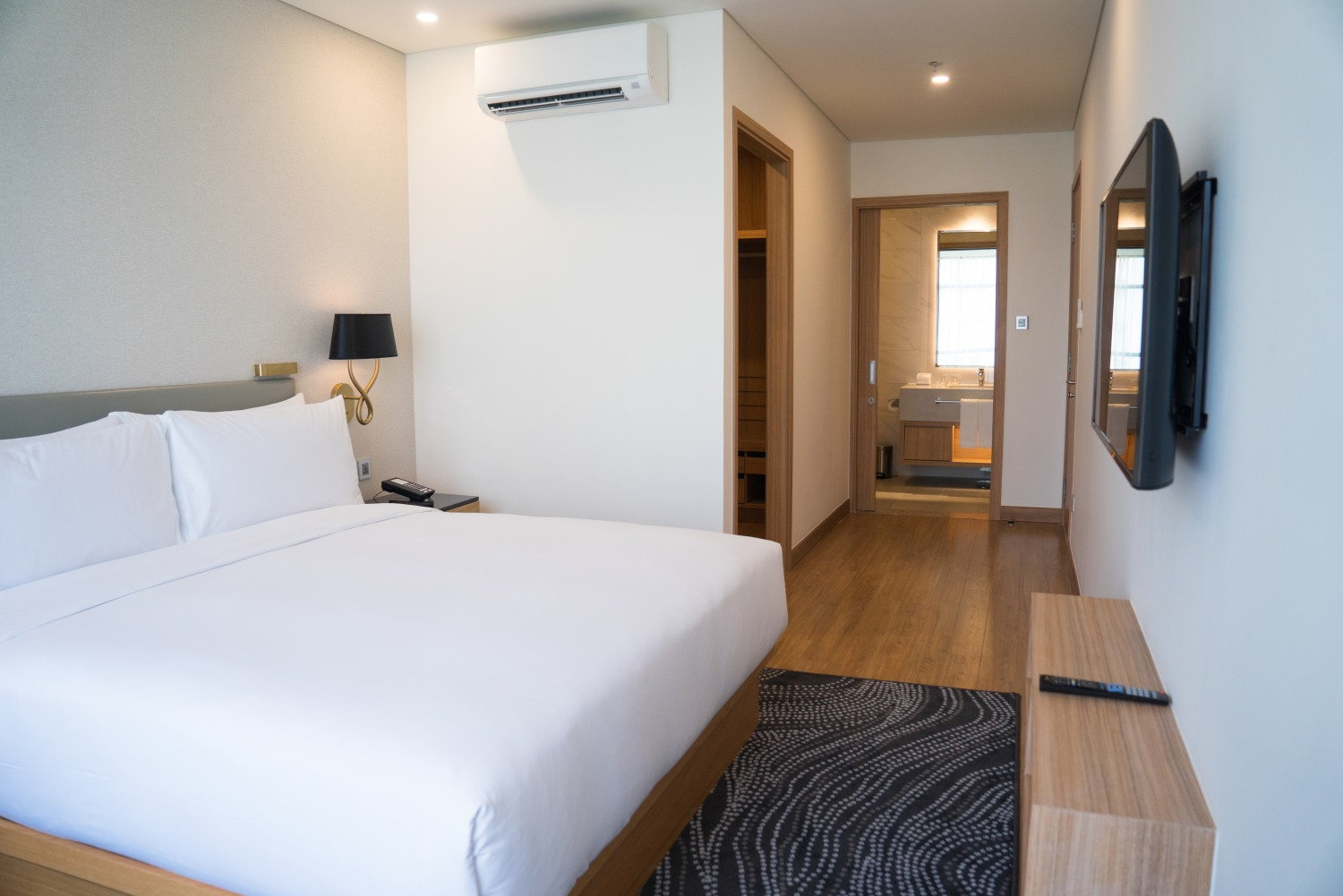 small hotel room interior with double bed bathroom